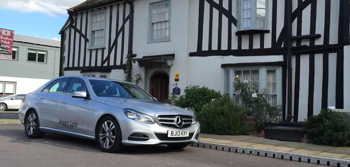 An image of one of our cars outside a thatched house.